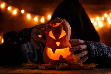 Photo of halloween pumpkin cut in shape of face with witch