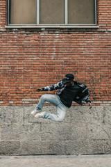 Black Man Jumping Besides a Brick Wall