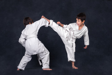 two boys of the karateka in a white kimono battle or train