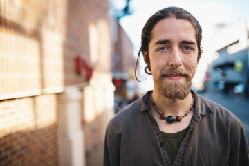 Portrait of young traveler man standing on city sidewalk