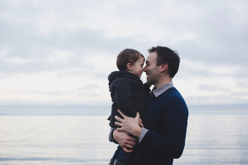 Young father man snuggling with toddler child near ocean in west coast winter