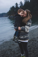 Pretty young woman snuggling with toddler child near ocean in west coast winter