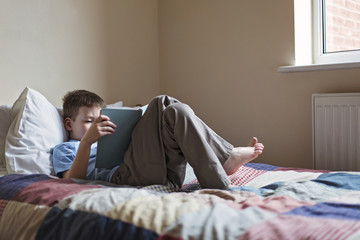 Boy reading a book while lying on a bed