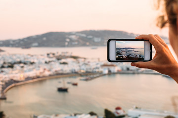 Woman photographing  with smartphone at  sunset
