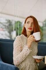 Beautiful redhead woman holding a cup of tea in cafe