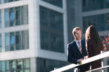 Businessman and Businesswoman in front of a Corporate Building