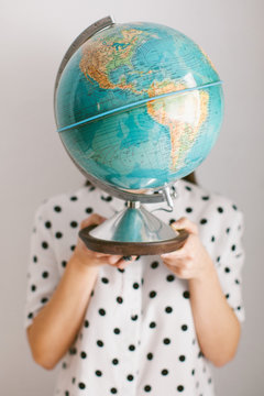 Woman covering her face with a globe against gray background