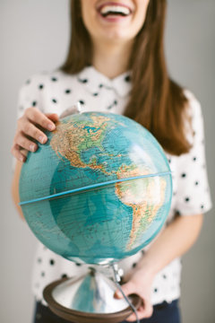 Smiling woman holding globe standing against white background