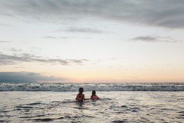 Two young sisters swimming in ocean together at sunset