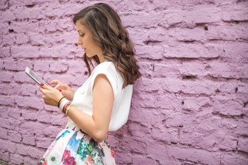 Cute brunette using silver tablet in front of a pink wall