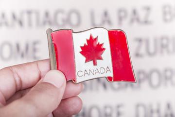 Hand holding Canada flag fridge magnet