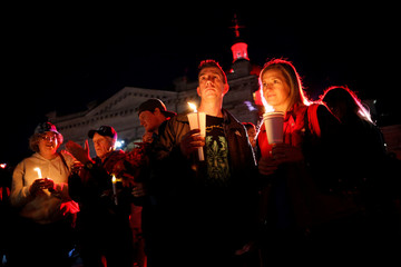 People hold candles during a vigil for the late Tragically Hip frontman Gord Downie in Kingston
