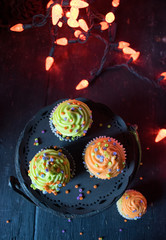 Halloween cupcakes in spooky setting with orange lights top view