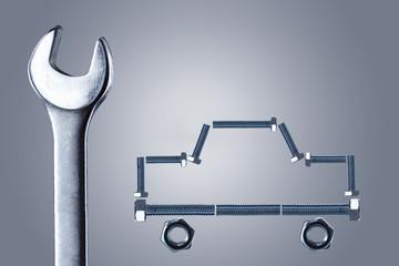Образ автомобиля из металлических болтов и гаечный ключ.Концепция ремонта.