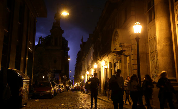 People walk on a street as lightning illuminates the sky in Buenos Aires