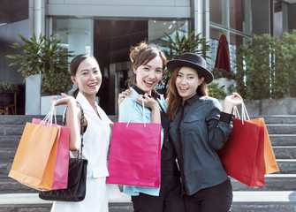 Happy young asian women with a group of friend and shopping bags smiling and looking at camera, woman feeling happy, enjoy, cheerful at shopping mall.
