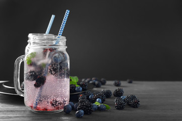 Refreshing water with blackberries and blueberries in mason jar on table