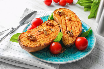Plate with baked sweet potato and fresh tomatoes on table