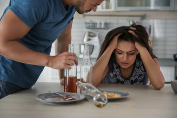 Young woman and drunk man at home