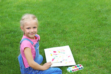 Cute little girl painting picture, outdoors