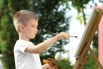 Cute little boy painting picture, outdoors