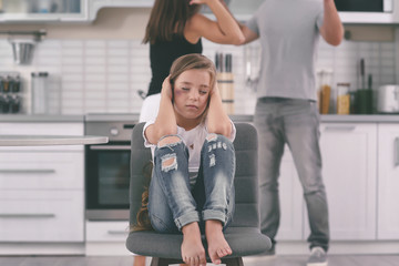 Little girl with bruise covering ears while her parents fighting on background. Domestic violence concept