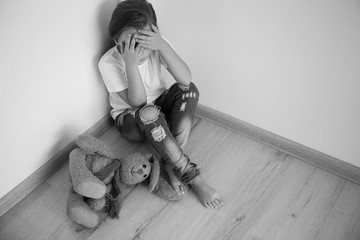 Scared little girl sitting in corner of room. Domestic violence concept