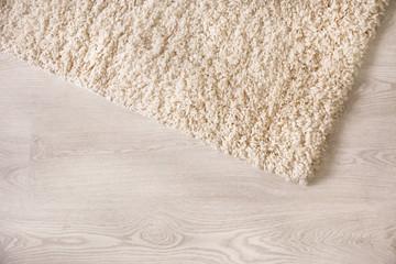 White soft carpet on wooden floor, closeup