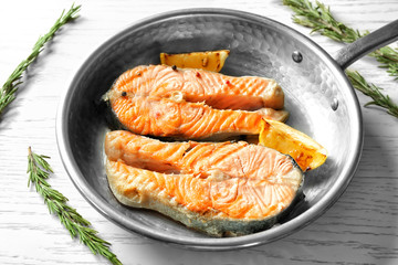 Frying pan with delicious salmon steaks on table