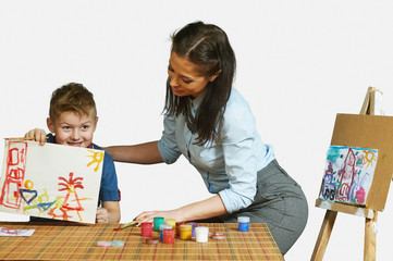The woman helps the boy to develop the ability to painting . Young mother and son have been drawing . Isolated image