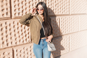Fashion close up portrait stylish woman in fall spring casual outfit walking in city. Street style.young beautiful woman in street background in khaki bomber coat,jeans and bag,autumn fashion trend.