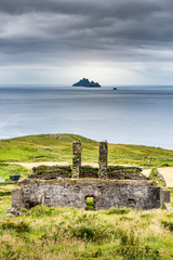 the ruins of an old farmhouse or factory face the Skellig islands on the coast of Kerry, Ireland