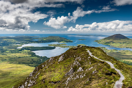 The hiking trail at the top of Diamond Hill in Connemara National Park, Ireland. Behind, the sun plays with the clouds reflected in the sea.