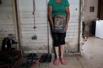 Aurea Esther Gonzalez holds a bible dirty with mud, after Hurricane Maria hit the island in September, in Toa Baja, Puerto Rico