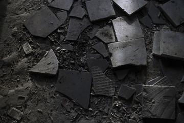 Broken tiles, cigarette boxes, cigarette butts and trash at the floor in dark sand