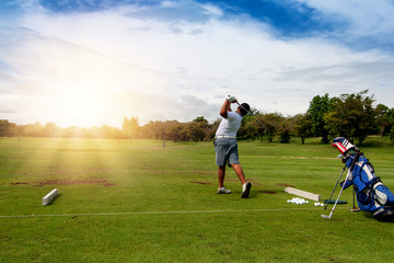 13-year-old Asian boy  playing golf on a golf course in the sun