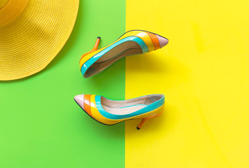 Fashion woman accessories set. Trendy fashion colorful shoes heels, stylish yellow big hat. Colorful green and yellow background.  Lifestyle Concept.