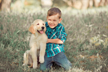 Cute handsome boy teen with blue eyes playing outdoor with amazing white pink labrador retriever puppy enjoying summer sunny day vacation weekend with full happyness.Happy smiling kid with best friend