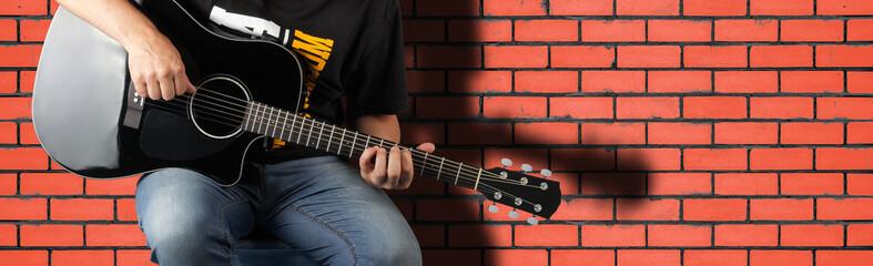 Music - Fragment man play a black acoustic guitar