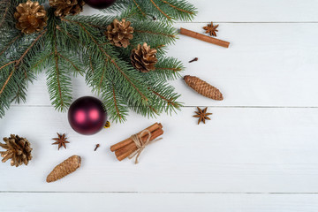 Christmas background with fir tree branches, glass balls, pine cones, cinnamon sticks and star anise on white wooden background, free space. Holiday greeting card. Flat lay, top view with copy space