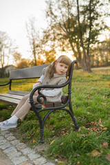 Little girl sits on the bench in the park