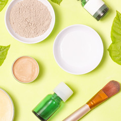 Top view of different cosmetics products on yellow background