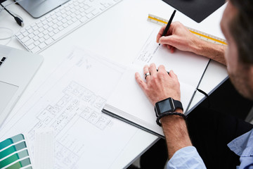 Cropped image of architect writing on diary while planning at desk in creative office