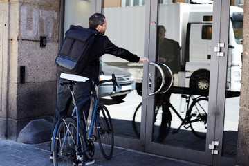 Rear view of businessman with bicycle opening glass door on sunny day