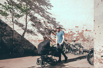 Full length of father pushing baby carriage on footpath against wall