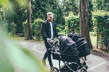 Full length of man pushing baby carriage on footpath