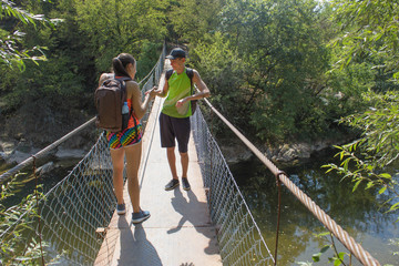 Traveler travel on the artificial roadway of the suspension bridge. Active hikers. Active and healthy lifestyle on summer vacation and weekend tour. young Tourists With Backpacks travel