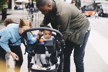 Parents with toddler by baby stroller on sidewalk in city