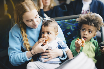 Mother feeding baby boy while sitting with son in bus