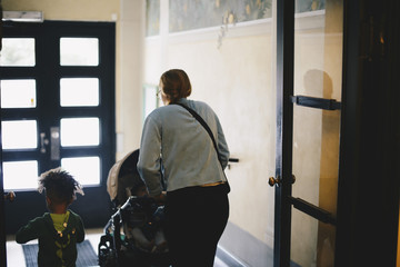 Rear view of mother pushing baby stroller while walking with son at doorway